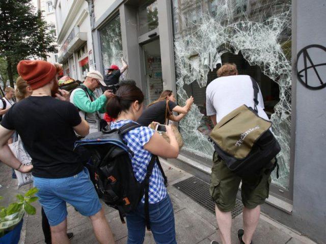 Gaffer:Schaulustige fotografieren den geplünderten Drogeriemarkt im Hamburger Schanzenviertel. Foto:Bodo Marks/dpa