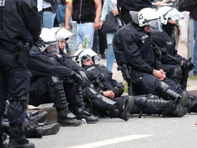 Völlig erledigt: Polizisten ruhen sich am Rande der Demonstration «Grenzenlose Solidarität statt G20» aus. Foto: Sebastian Willnow/dpa