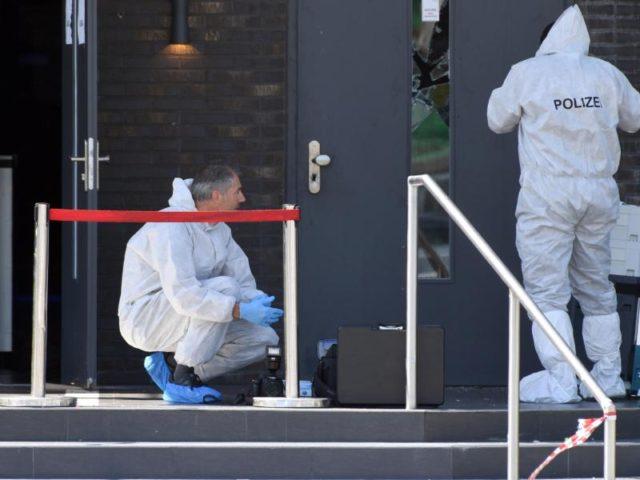 Zwei Polizisten in weißen Schutzanzügen sichern vor der Diskothek Spuren. Foto: Felix Kästle/dpa