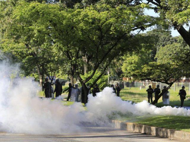 Mitglieder der Nationalgarde werfen Tränengas gegen Demonstranten, die zu der Kaserne Paramacay in Valencia marschieren. Foto: Juan Carlos Hernandez/dpa