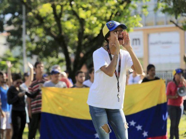 Anwohner schreien nahe der Kaserne Paramacay in Valencia Parolen gegen Maduros Regierung. Foto: Juan Carlos Hernandez/dpa