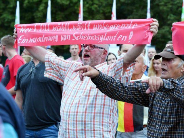 Menschen bekunden beim Wahlkampfauftritt der CDU in Apolda ihren Unmut. Foto: Jens Kalaene/dpa