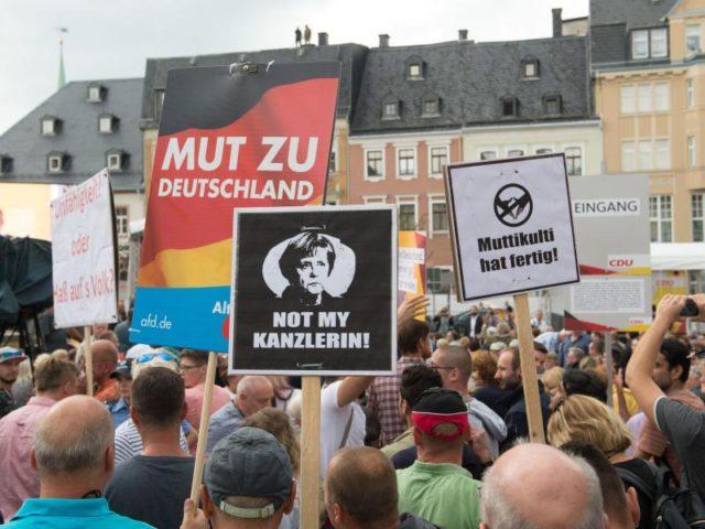 Protestler stehen während eines Wahlkampfauftritts von Bundeskanzlerin Merkel auf dem Marktplatz in Annaberg-Buchholz. Foto: Sebastian Kahnert/dpa