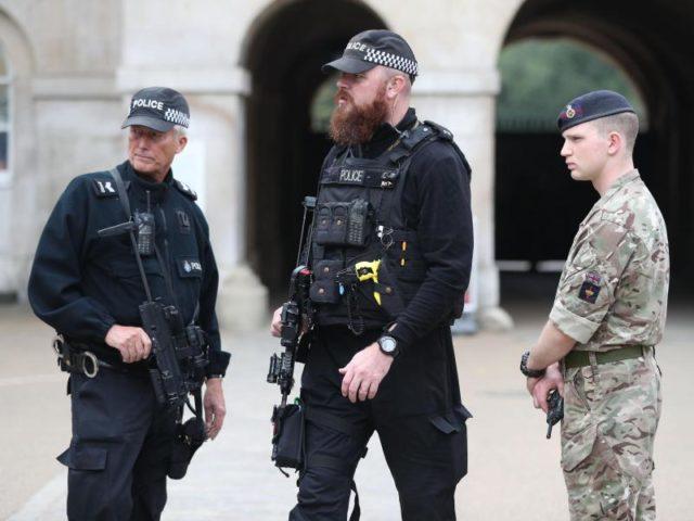 Bewaffnete Polizisten und ein Soldat sichern den Eingang zu Horse Guards in Whitehall in London. Foto: Jonathan Brady/dpa