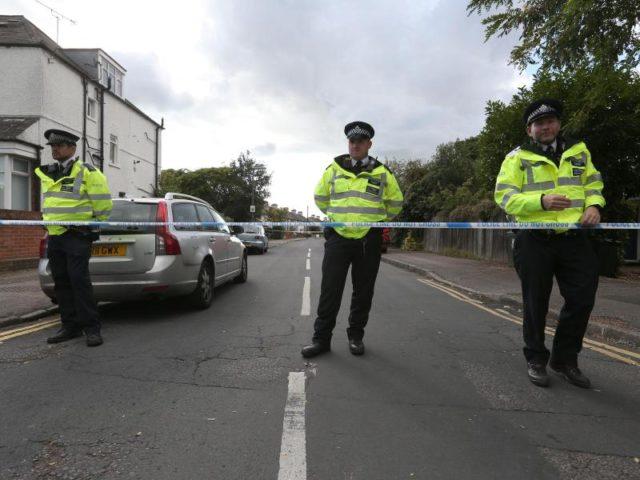 Polizisten stehen zur Absicherung einer Hausdurchsuchung in Sunbury-on-Thames auf einer gesperrten Straße. Foto: Jonathan Brady/dpa