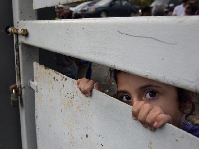 Puertoricanische Kinder beobachten Mitglieder der US-Nationalgarde, die Hilfsgüter für die von Hurrikan «Maria» betroffenen Gebiete ausladen. Foto:Carol Guzy/dpa