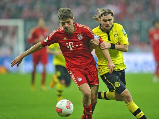 Münchens Thomas Müller (l) im Kampf um den Ball mit BVB-Spieler Marcel Schmelzer. Die Bayern siegen im Viertelfinale mit 1:0. Foto:Marc Müller/dpa