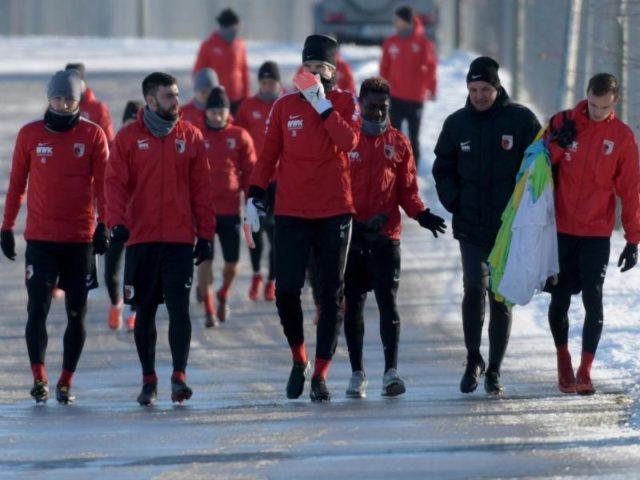 Auf verschneiter Straße begibt sich Augsburgs Trainer Manuel Baum mit den Spielern zum Training. Foto: Stefanf Puchneer/dpa