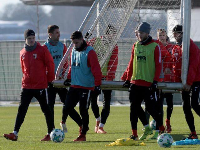 Zum Trainingsauftakt tragen die Spieler des FC Augsburg ein Tor auf den Platz. Foto: Stefan Puchner/dpa