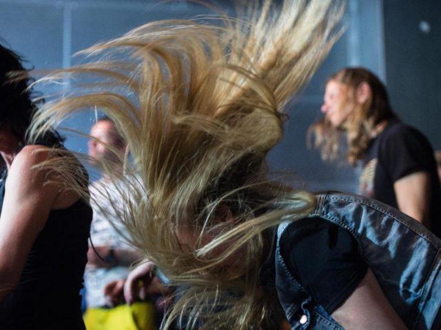 Weiblicher Metal-Fan beim Headbanging. Foto: Henrik Josef Boerger/dpa