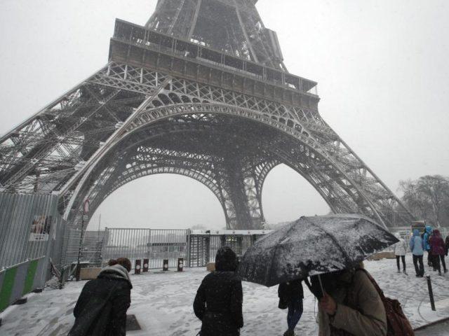 Fußgänger am Eiffelturm. Das Pariser Wahrzeichen bleibt wegen des Winterwettersfür Besucher geschlossen. Foto: Francois Mori/AP/dpa