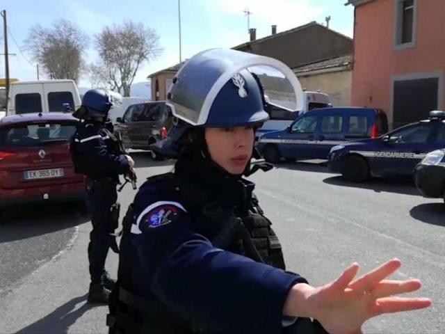 Polizisten sichern während einer Geiselnahme in einem Ort am Rande von Carcassonne eine Straße. Foto: La Depeche Du Midi/dpa