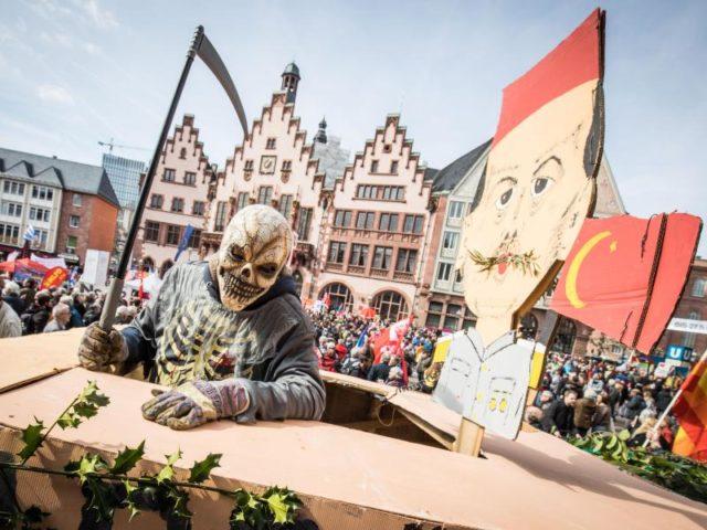 Ein als Tod verkleideter Demonstrant steht auf dem Frankfurter Römerberg auf einem Leopard-Panzer aus Pappe neben einem Bildnis des türkischen Präsidenten Erdogan. Foto: Frank Rumpenhorst/dpa