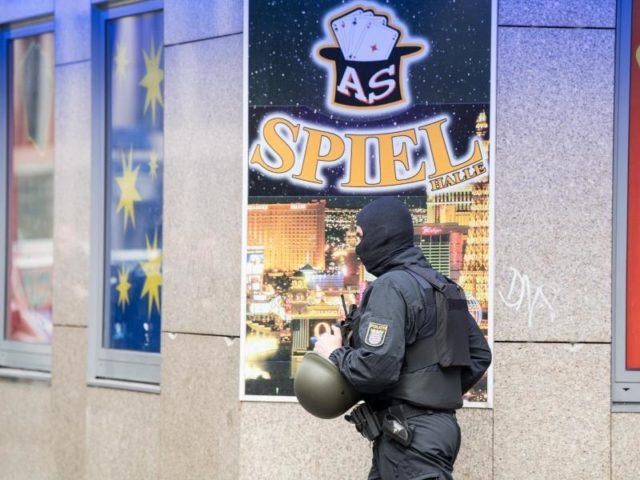 Ein vermummter Polizist geht im Frankfurter Bahnhofsviertel an einer Spielhalle vorbei, die Ziel einer Razzia ist. Foto: Fabian Sommer/dpa