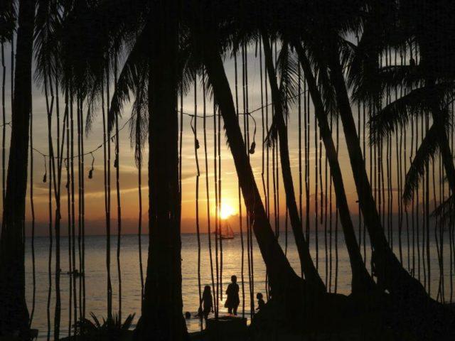 Menschen betrachten den Sonnenuntergang am Strand. Boracay ist nun für sechs Monate geschlossen. Foto: Aaron Favila, AP/dpa
