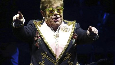 Elton John fährt im Rollstuhl durchs Museum