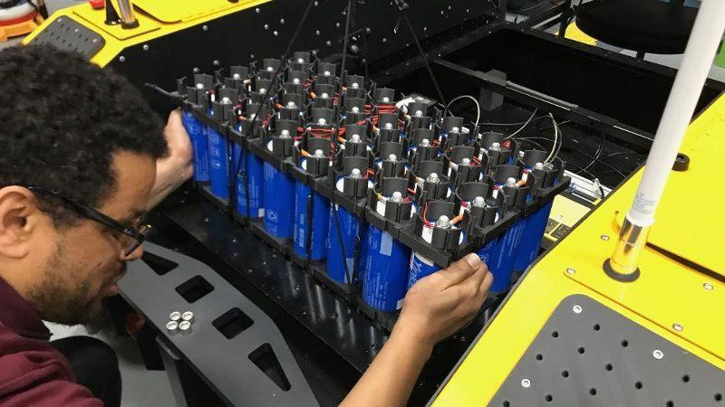 Ein Ingenieur der US-Army installiert eine Batterie im Testfahrzeug mit Stirlingmotor.