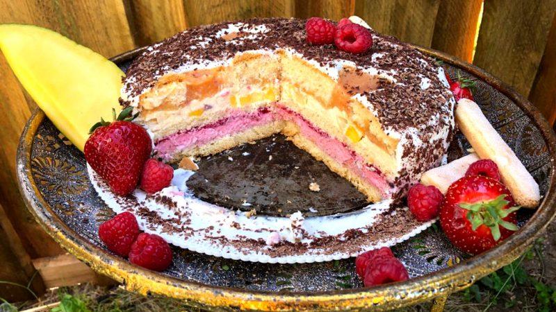 Angeschnittene Mango-Pfirsich-Himbeer-Torte