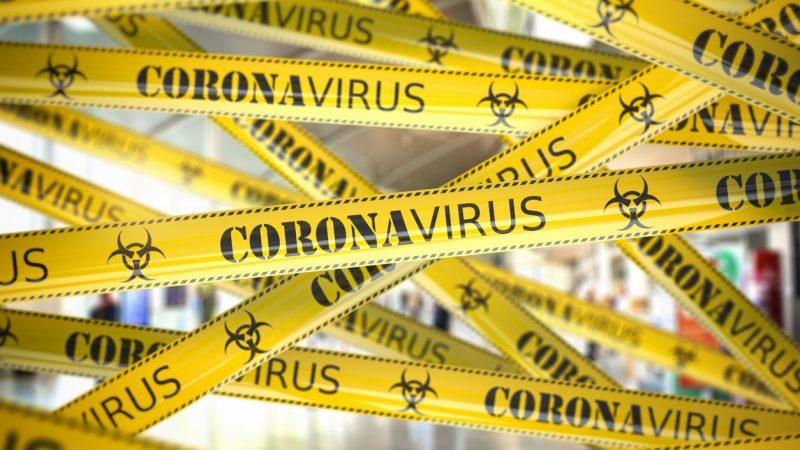 Achtung COVID-19! Gelbes Absperrband weist auf einen Quarantäne-Bereich hin.