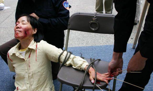 """Rekonstrukce jedné z metod mučení praktikované na vězněné následovníky Falun Gongu, v rámci takzvané """"převýchovy"""", při níž se mají vzdát své víry. (Se svolením Minghui.org)"""